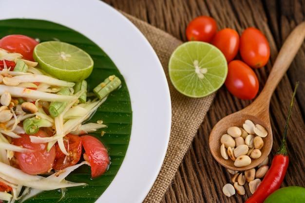 Papayasalat (som tum thai) auf einem weißen teller auf einem holztisch.