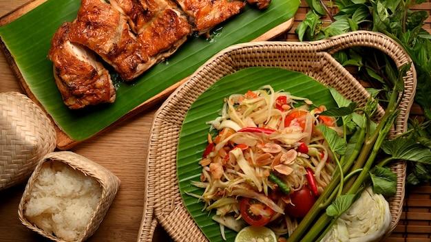 Papayasalat somtum mit gemüse, gegrilltem hähnchen nach thailändischer art und klebreis im thailändischen restaurant