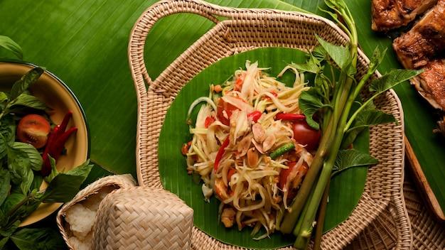 Papayasalat somtum serviert mit gegrilltem hähnchen nach thailändischer art und klebreis thailändisches traditionelles essen