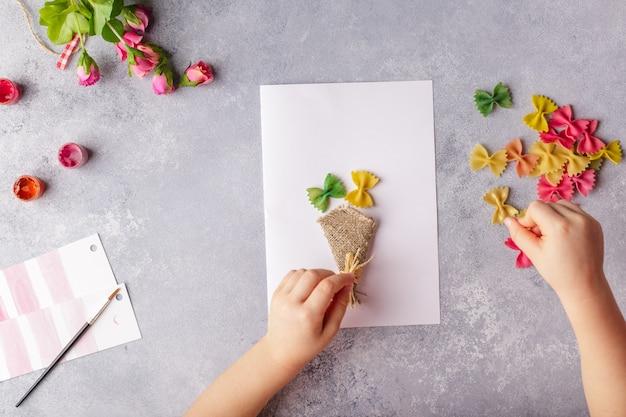 Papier basteln für muttertag, 8. märz oder geburtstag. kleines kind, das einen blumenstrauß aus farbigem papier und farbigen teigwaren heraus tut.