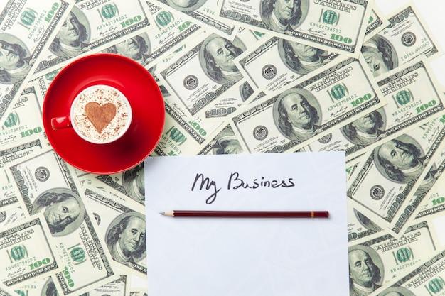 Papier, bleistift, tasse und dollar auf dem tisch liegen