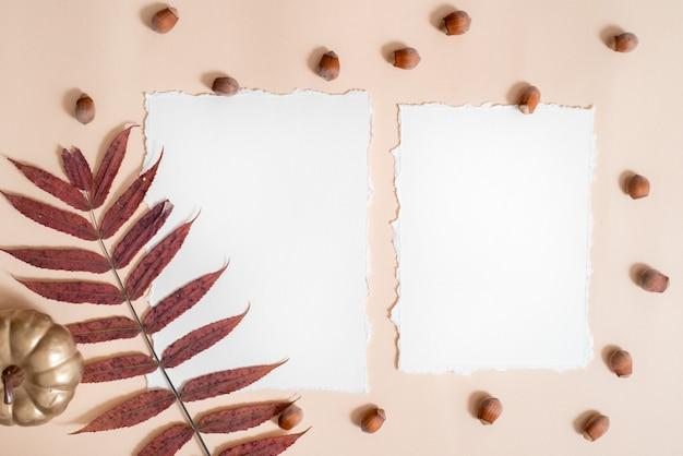 Papier für ihre notizen. zerrissenes papier trend.autumn zusammensetzung modell. nüsse, trockene blätter auf einem braunen hintergrund. warmer gestrickter roter pullover und schal, papierblätter und ein notizbuch. trend zerrissenes papier.