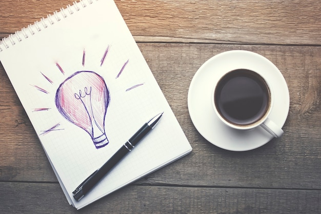 Papier, glühbirne, smartphone, stift und tasse kaffee auf schreibtisch aus holz