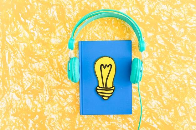 Papier herausgeschnittene gelbe glühlampe auf geschlossenem notizbuch mit kopfhörer auf strukturiertem hintergrund