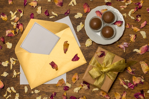 Papier in brief in der nähe von teller mit süßigkeiten und geschenkkarton zwischen trockenen blättern