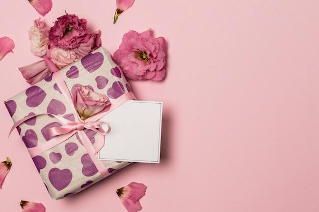Papier in der nähe von geschenk und blumen und blütenblätter