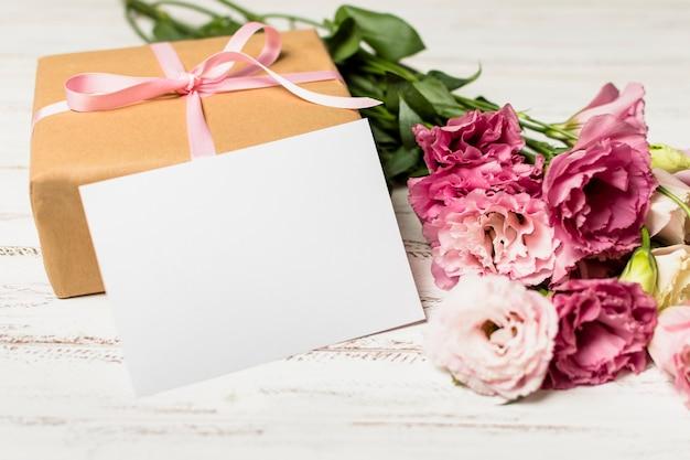 Papier in der nähe von geschenkbox und blumen