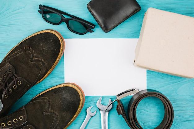 Papier in der nähe von männlichen accessoires, box und schuhen
