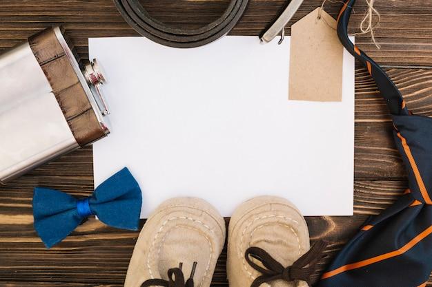 Papier in der nähe von männlichen accessoires und kinderschuhen
