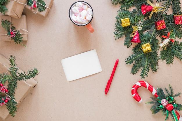 Papier in der nähe von stift, geschenkkartons, weihnachtszweig und tasse