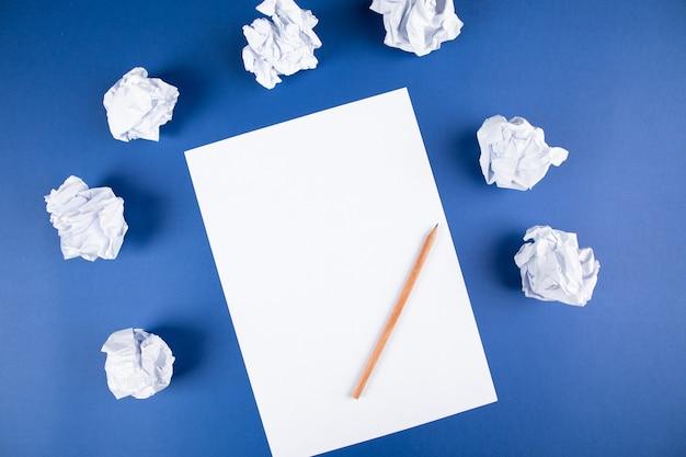 Papier mit bleistift und papierbündeln auf einer blauen oberfläche