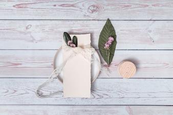 Papier mit den Blumenblättern und Band auf Platte nahe Blatt