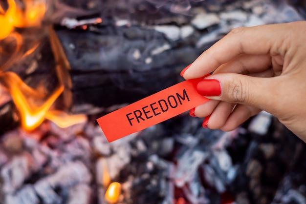 Papier mit der aufschrift freiheit über einem lagerfeuer, bevor es verbrannt wird