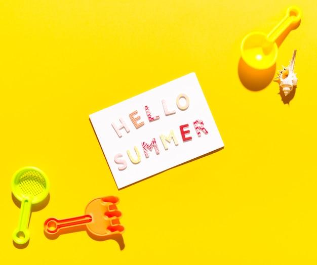 Papier mit der aufschrift hallo sommer und schaufeln für sandkästen