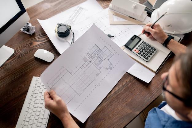 Papier mit skizze gehalten von zeitgenössischem ingenieur, der blaupause betrachtet und notizen im notizbuch durch arbeitsplatz macht