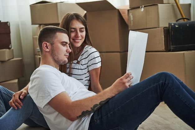 Papier mit wichtigen informationen. fröhliches junges paar in ihrer neuen wohnung. konzeption des umzugs.