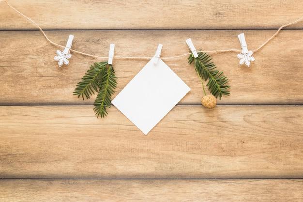Papier nahe tannenzweigen und schneeflocken auf thread