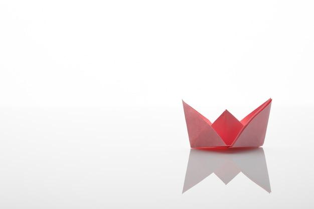 Papier origami rotes boot auf dem weißen