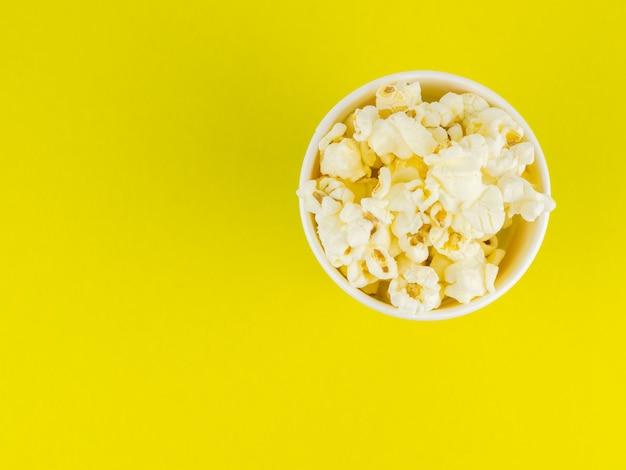 Papier popcorn tasse auf einer gelben oberfläche. platz für ihren text.