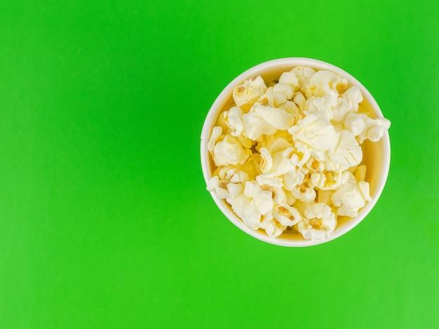 Papier popcorn tasse auf einer grünen oberfläche