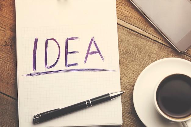 Papier, smartphone, stift und tasse kaffee auf schreibtisch aus holz