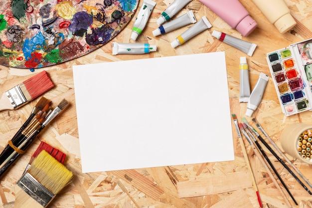 Papier umgeben von pinseln und farben