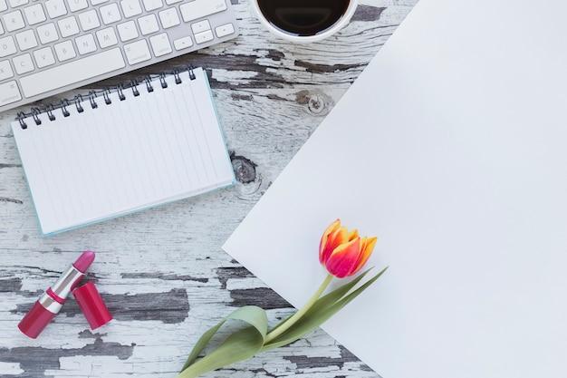 Papier und notizbuch nahe tulpenblume und -tastatur auf schäbigem schreibtisch