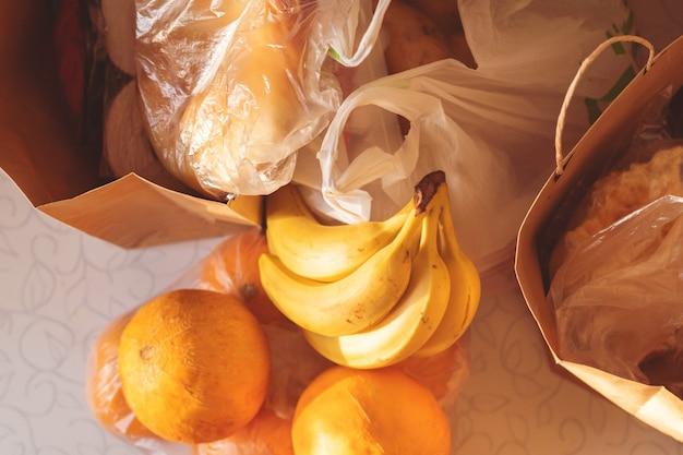 Papier- und plastiktüten-pakete mit essen auf dem tisch