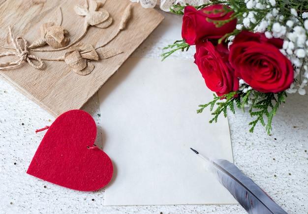 Papier und stift zum schreiben von liebesbotschaften mit buch und rosen