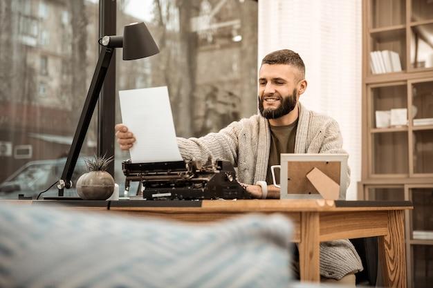 Papier von der schreibmaschine. lächelnder bärtiger schriftsteller, der mit seiner arbeit glücklich ist, während er in der langen strickjacke sitzt