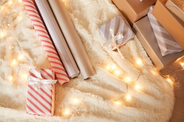 Papier zum verpacken von weihnachtsgeschenken und geschenkboxen auf weißem weichem teppich mit girlandenlichtern.