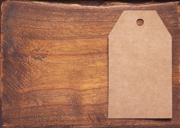 Papieranhängerpreis bei gealterter hölzerner hintergrundtexturoberfläche