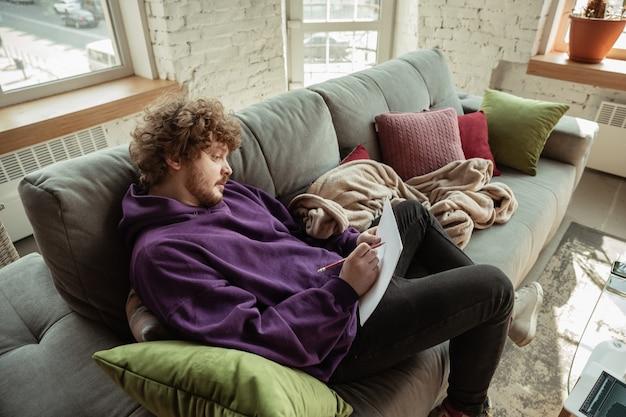 Papierarbeit. mann, der während der quarantäne von coronavirus oder covid-19 von zu hause aus arbeitet, remote-office-konzept. junger geschäftsmann, manager, der aufgaben mit smartphone, laptop, tablet erledigt, hat online-konferenz.