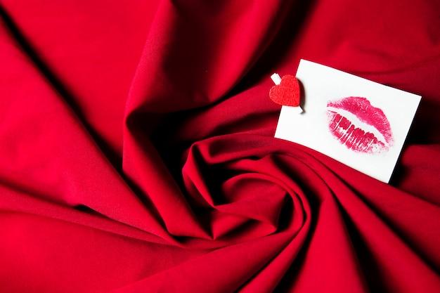 Papieraufkleber mit kuss auf rotem zerknittertem stoffhintergrund