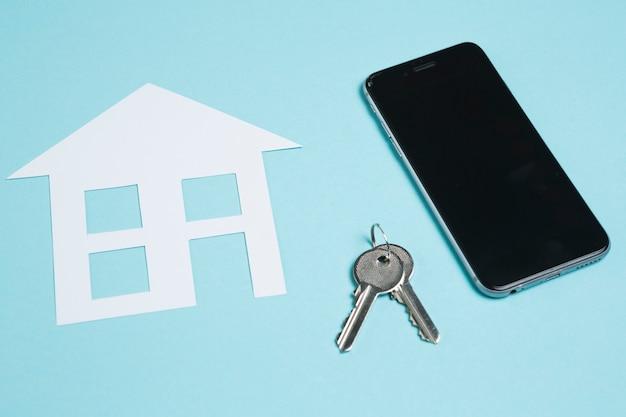 Papierausschnitt des hauses und der schlüssel mit mobiltelefon auf blauem hintergrund