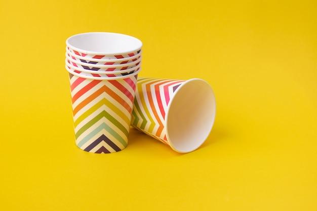 Papierbecher mit geometrischem muster auf gelbem hintergrund