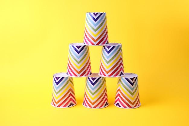 Papierbecher mit geometrischem muster haben die form einer pyramide auf gelbem hintergrund