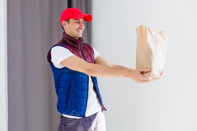 Papierbehälter für speisen zum mitnehmen. lieferbote trägt