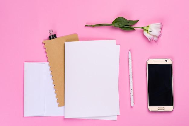 Papierblätter, telefon und notizbuch mit eustomarosa-blume