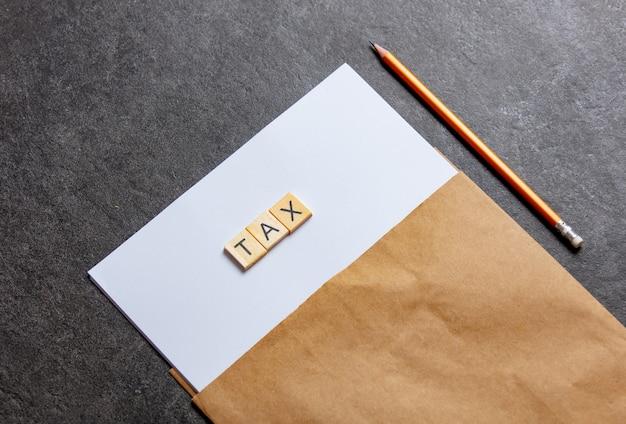 Papierblatt und bleistift mit steuerbuchstaben auf grauem tisch