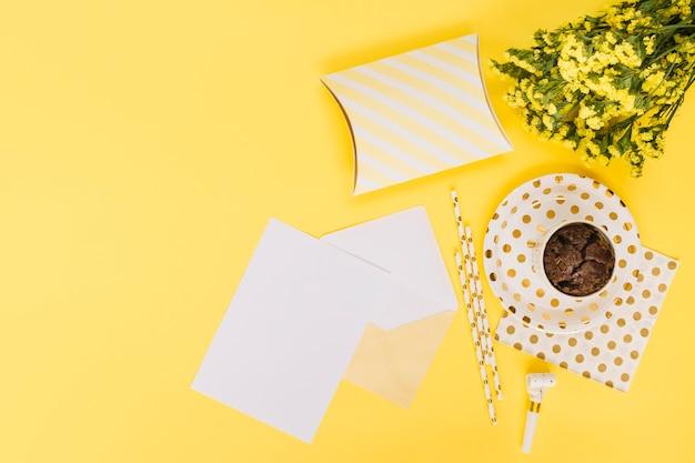 Papierblatt und partykram in der nähe von cupcake und geschenken