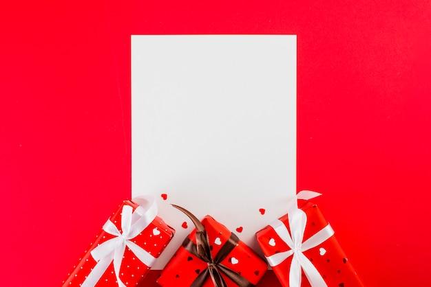 Papierblatt und valentinstaggeschenke auf rot