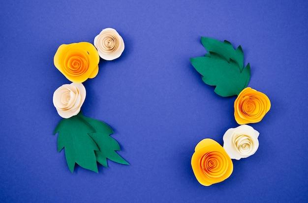 Papierblumen und blätter auf blauem hintergrund