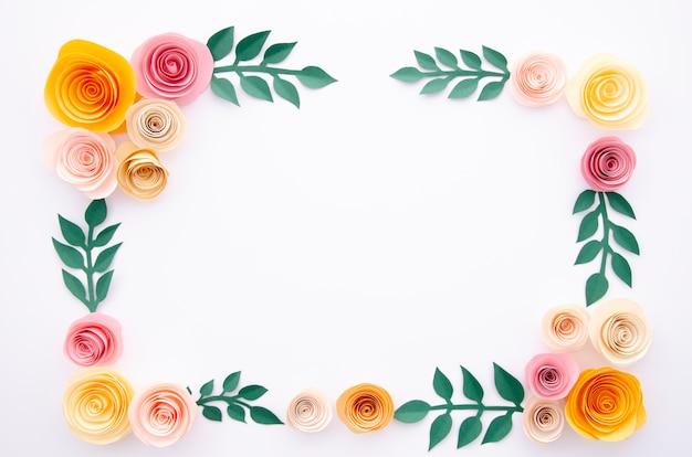 Papierblumen und blätter auf weißem hintergrund