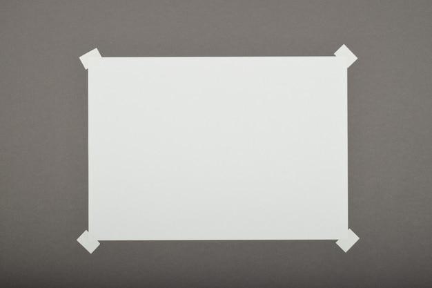 Papierbogen mit aufkleber auf grauem hintergrund isoliert