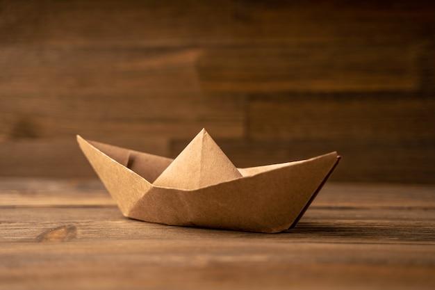 Papierboot auf einem hölzernen hintergrund