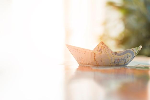 Papierboot auf sonnigem hintergrund
