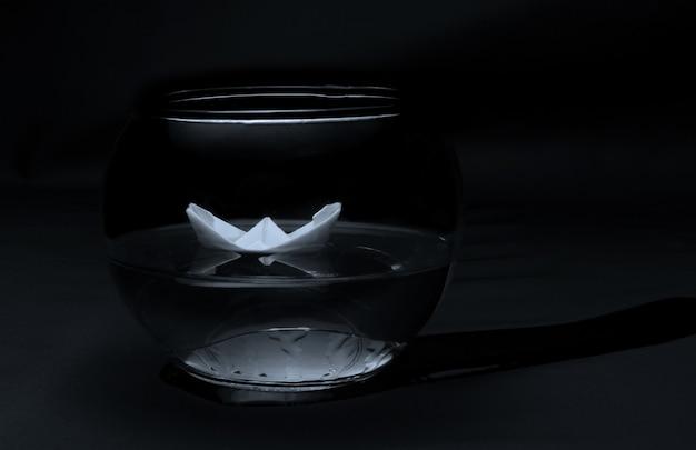 Papierboot schwimmt in einem kaputten aquarium