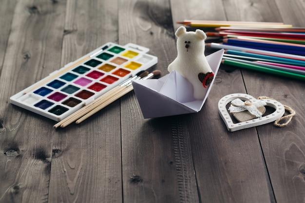 Papierboot und stofftier auf holztisch