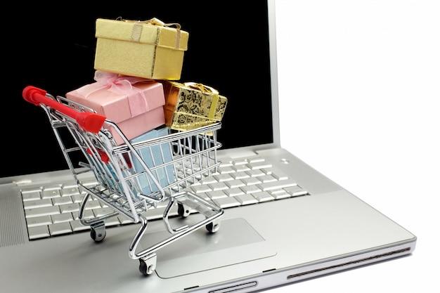 Papierboxen in einem einkaufswagen auf einer laptoptastatur. ideen zum e-commerce, eine transaktion zum kauf oder verkauf von waren oder dienstleistungen online.